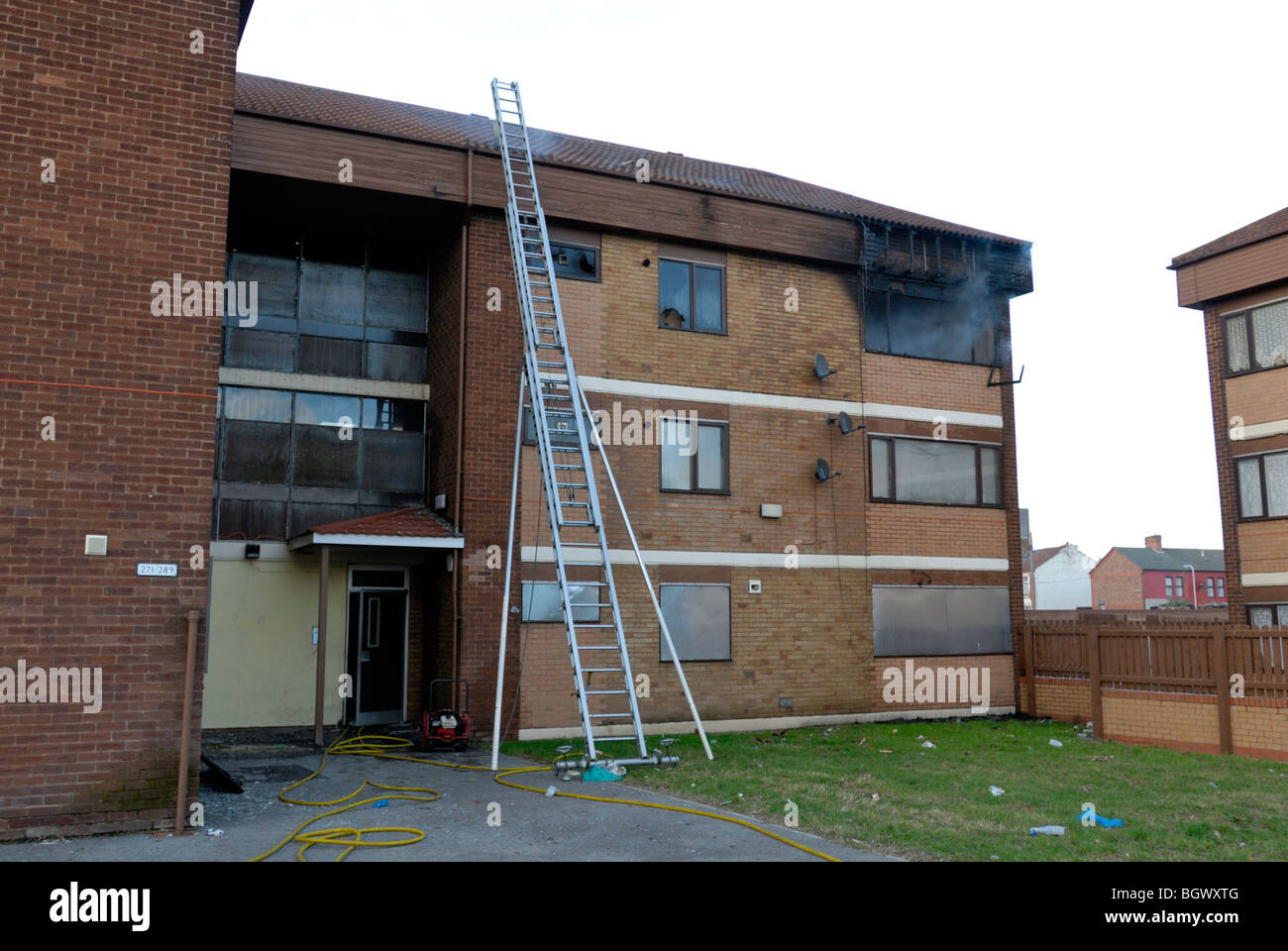 Top floor flat on fire with 135 ladder pitched against wall - Stock Image