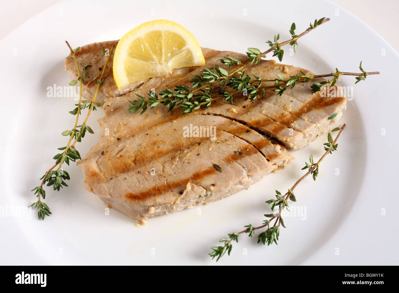 A grilled tuna steak, garnished with sprigs of thyme, on a plate with a wedge of lemon - Stock Image