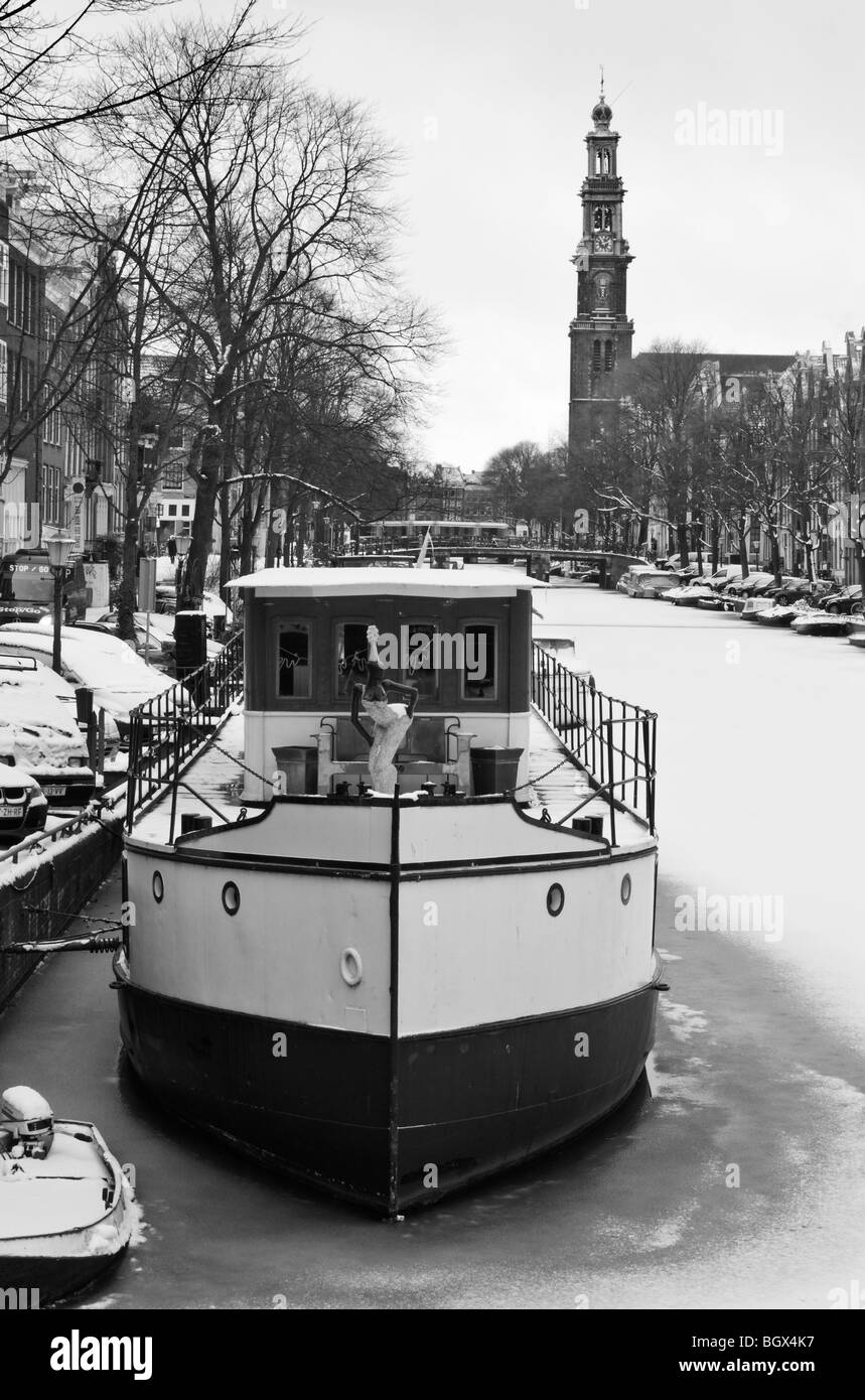 House boat on frozen Amsterdam canal, with the Westertoren (Western Church Tower) in the background - Stock Image