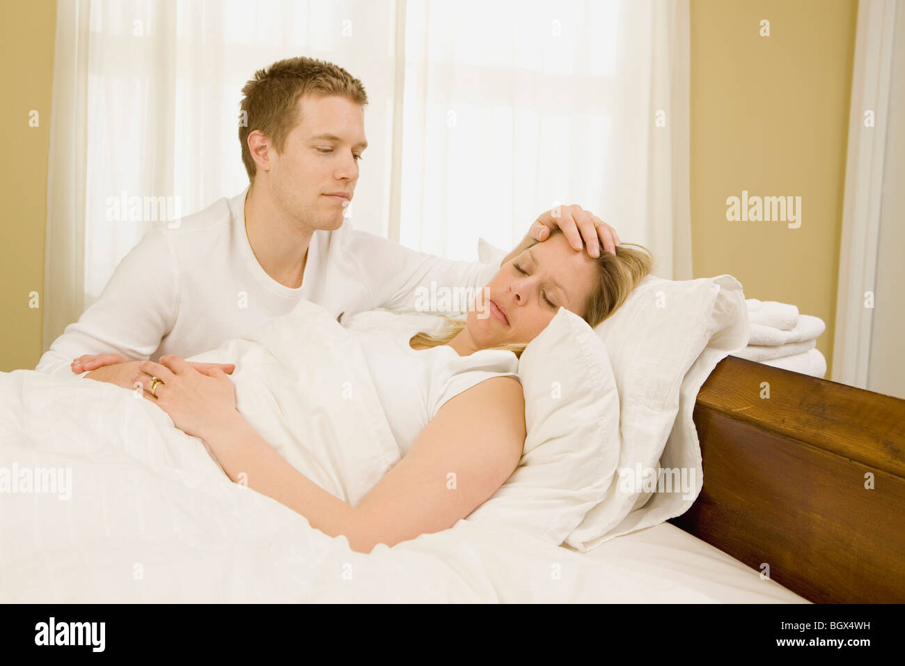 Loving Husband Caring For Sick Wife In Bed Stock Photo
