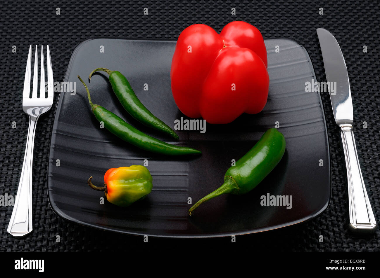 Table setting with cutlery and black plate with sweet bell and hot chili peppers - Stock Image