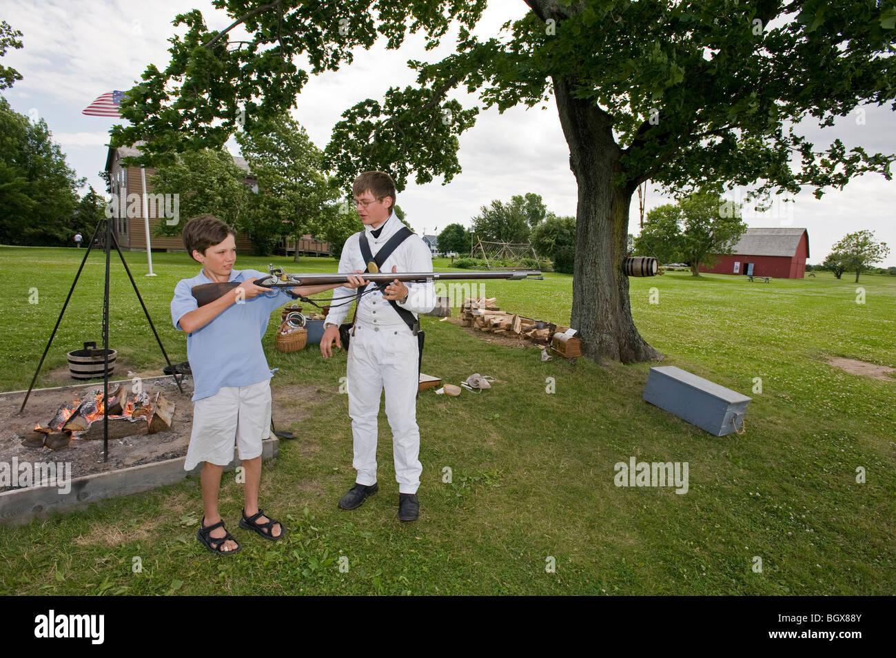Teen boy holding War of 1812 reenactor's musket. - Stock Image
