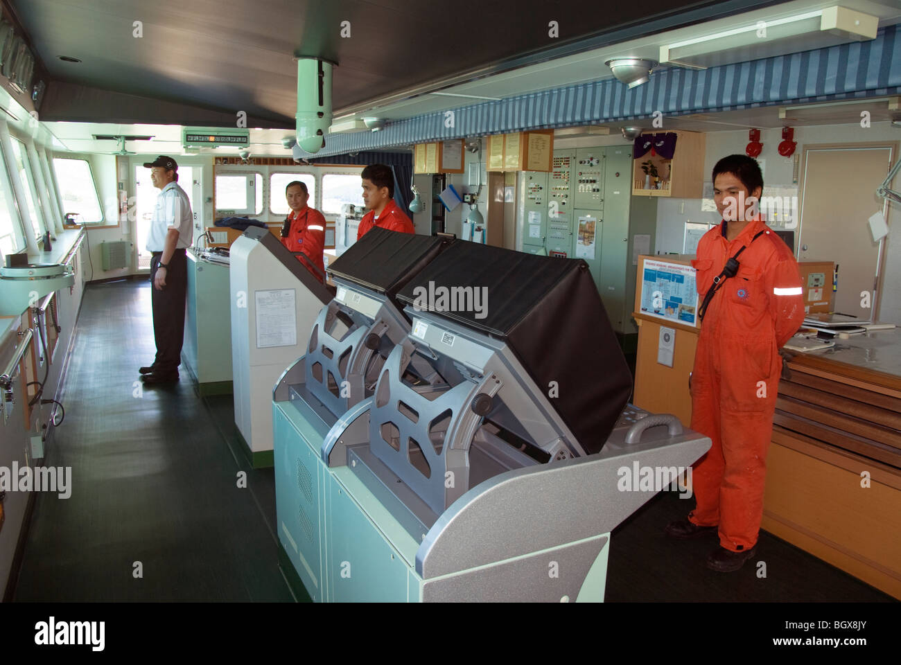 Captain and crew members on bridge of a ship entering port. - Stock Image