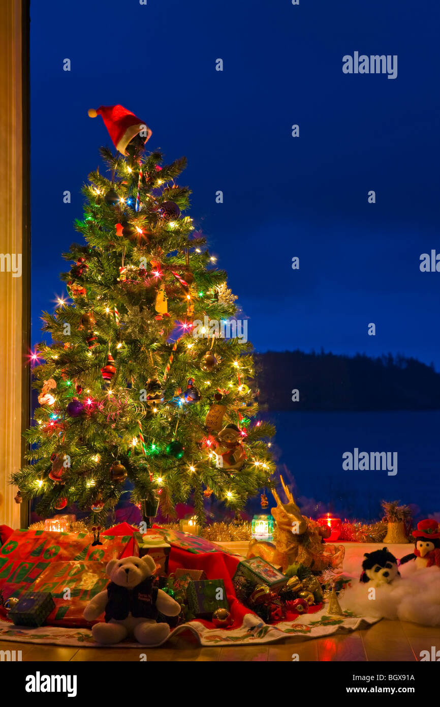 christmas tree with lights decorations and gifts in a window at dusk the