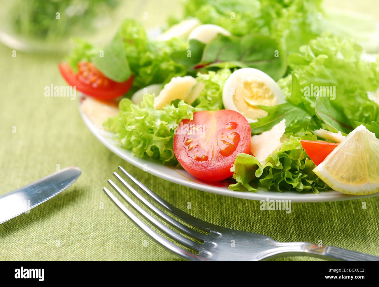 Fresh salad with tomato and quail eggs in a white bowl on a green tablecloth - Stock Image