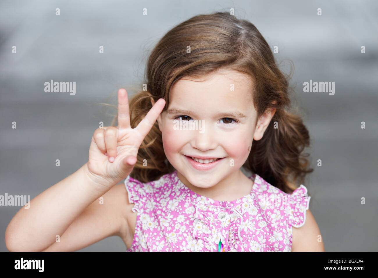 young girl holding up three fingers - Stock Image