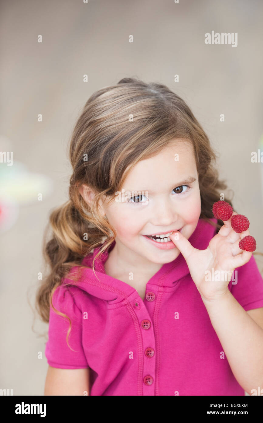 young girl eating berries from fingers - Stock Image
