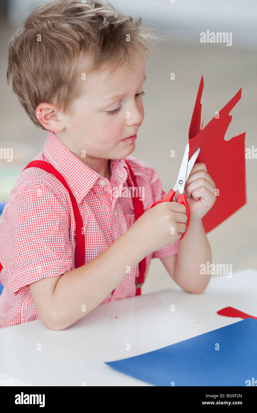 young boy with paper and scissors - Stock Image