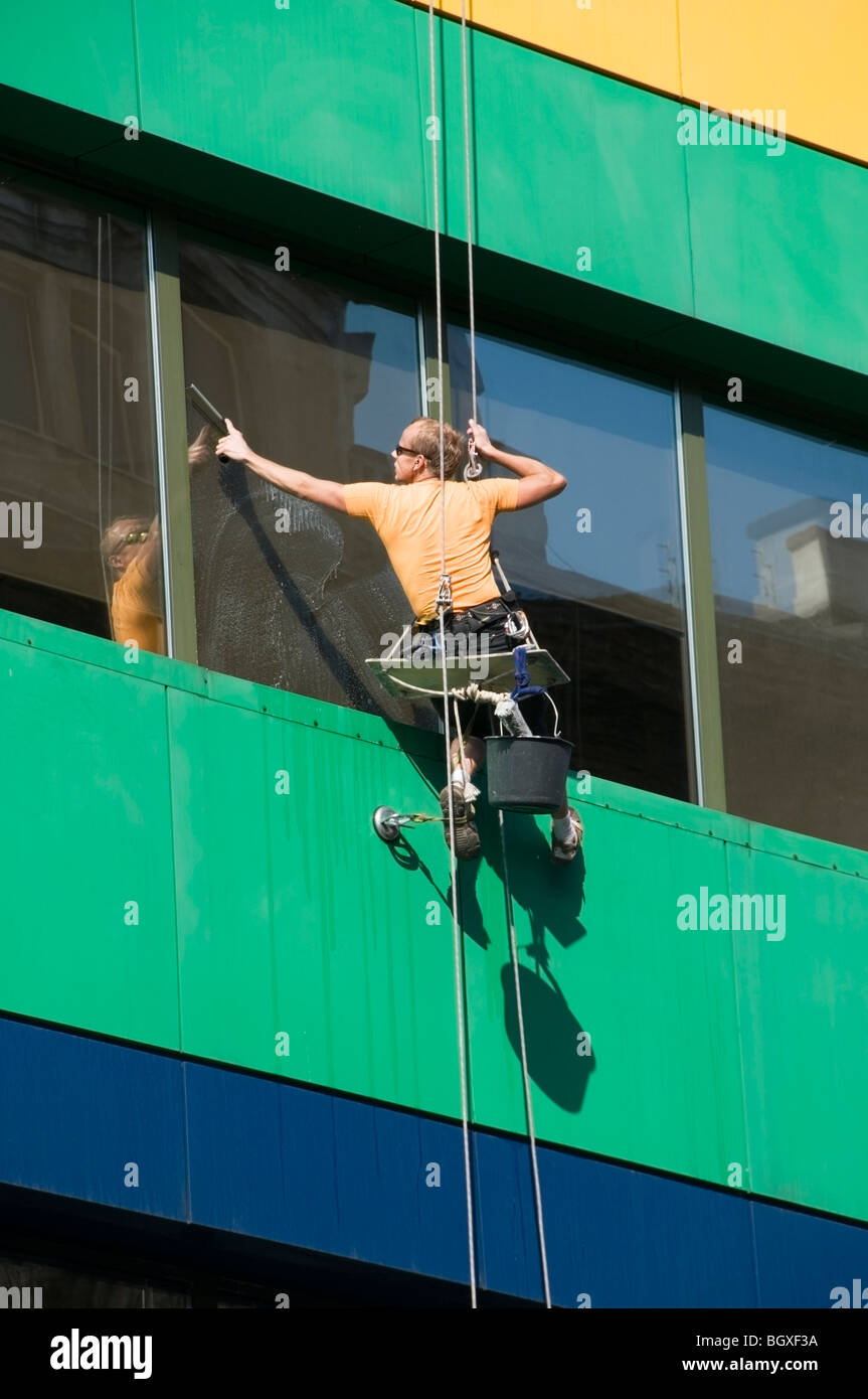Close-up of one office window cleaner suspended high up in a seat harness on an Abseiling Rope washing windows, - Stock Image