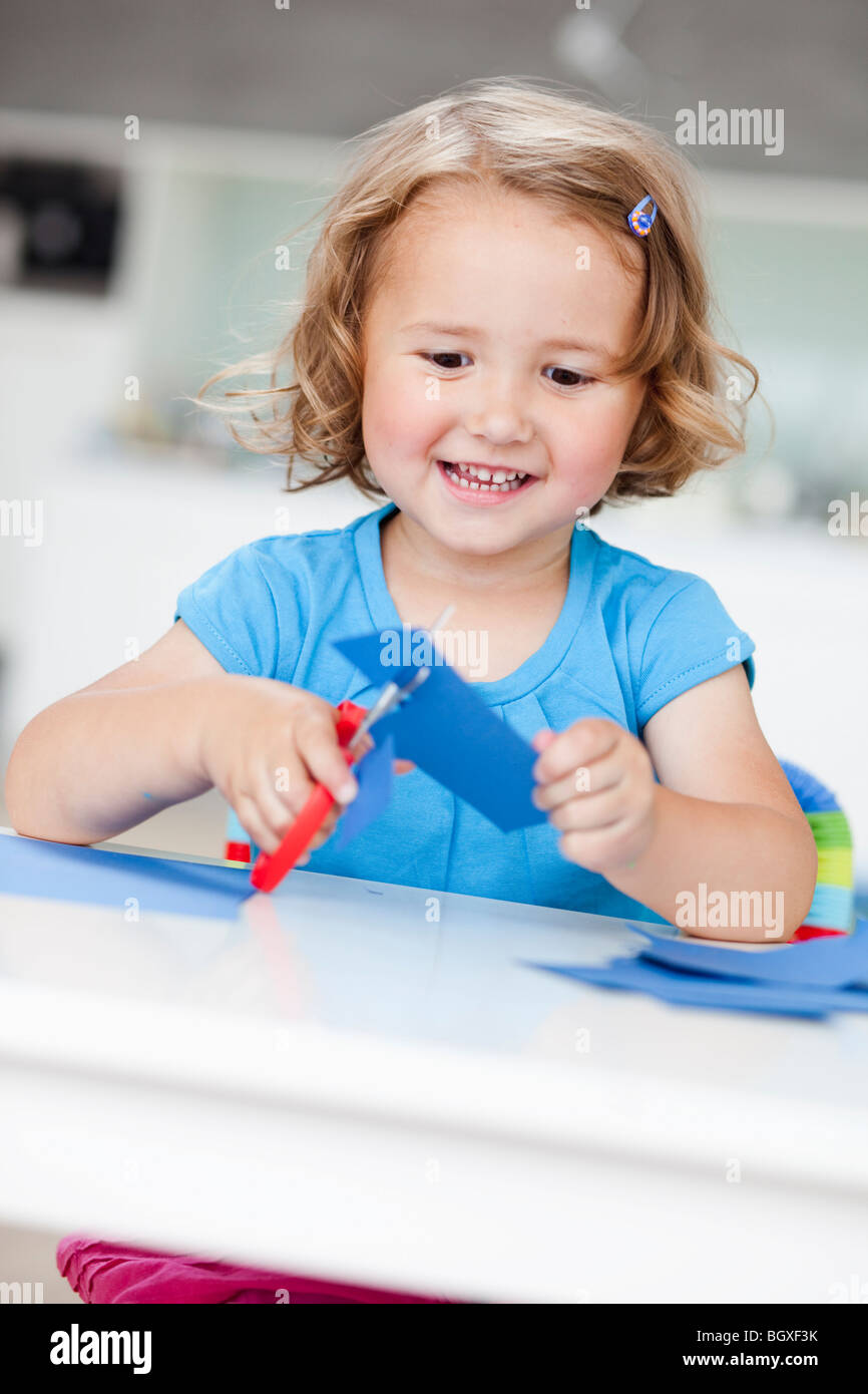 young girl using paper and scissors - Stock Image