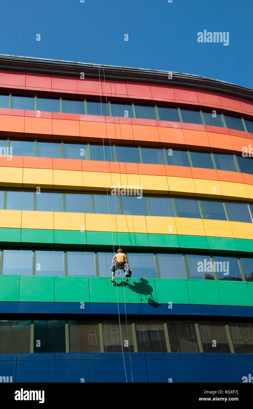 One office Window cleaner suspended high up in a seat harness on an Abseiling Rope washing windows, Warsaw, Poland, - Stock Image