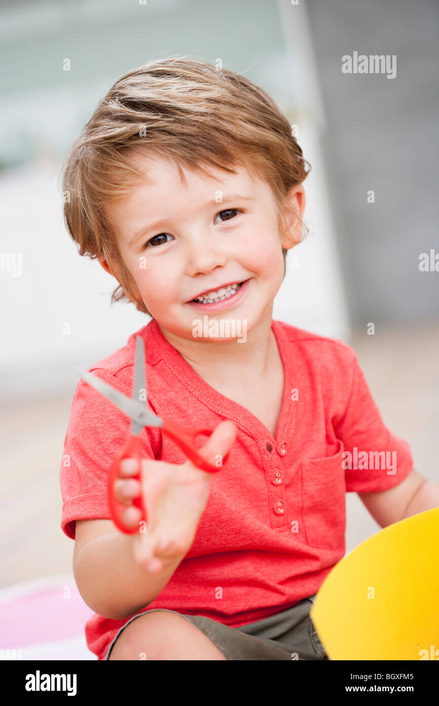 young boy playing with scissors - Stock Image