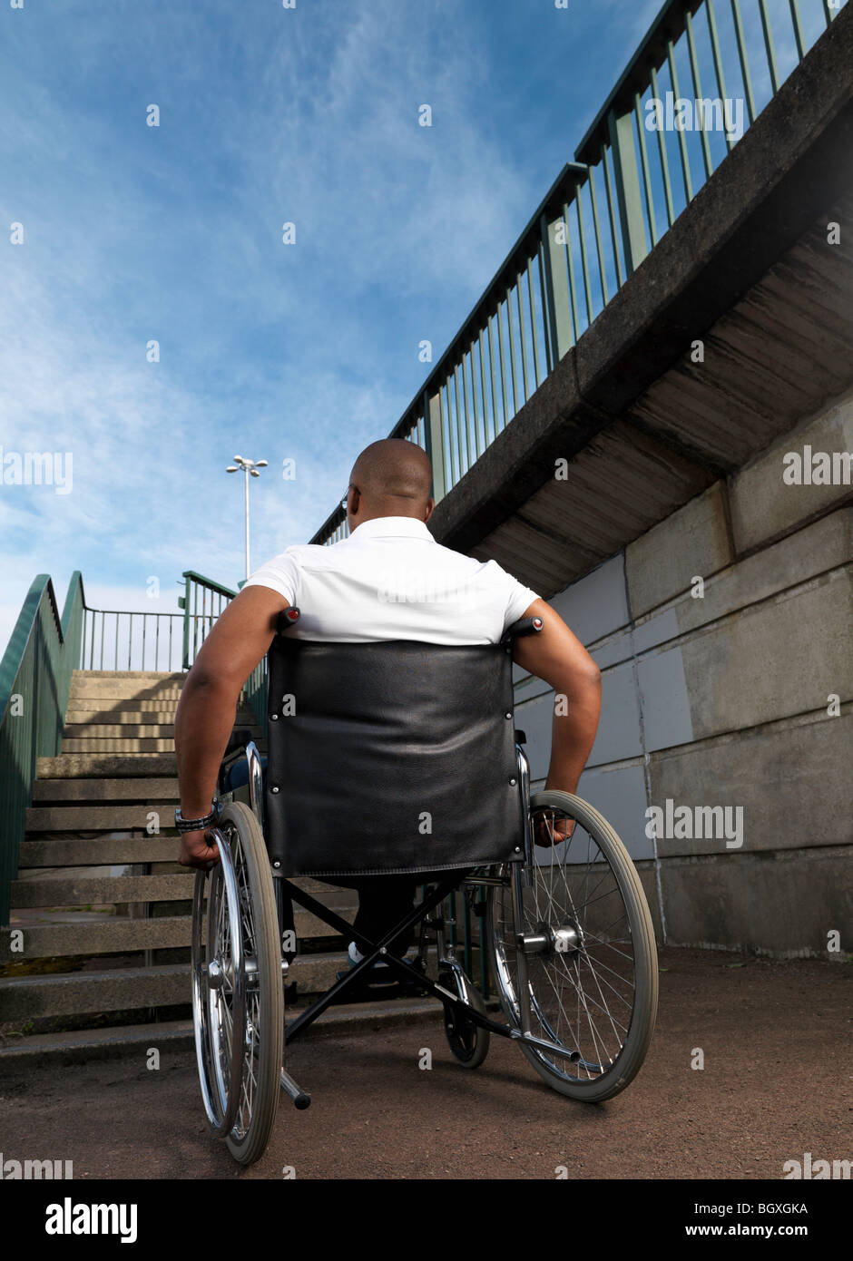 man in wheelchair in front of steps - Stock Image