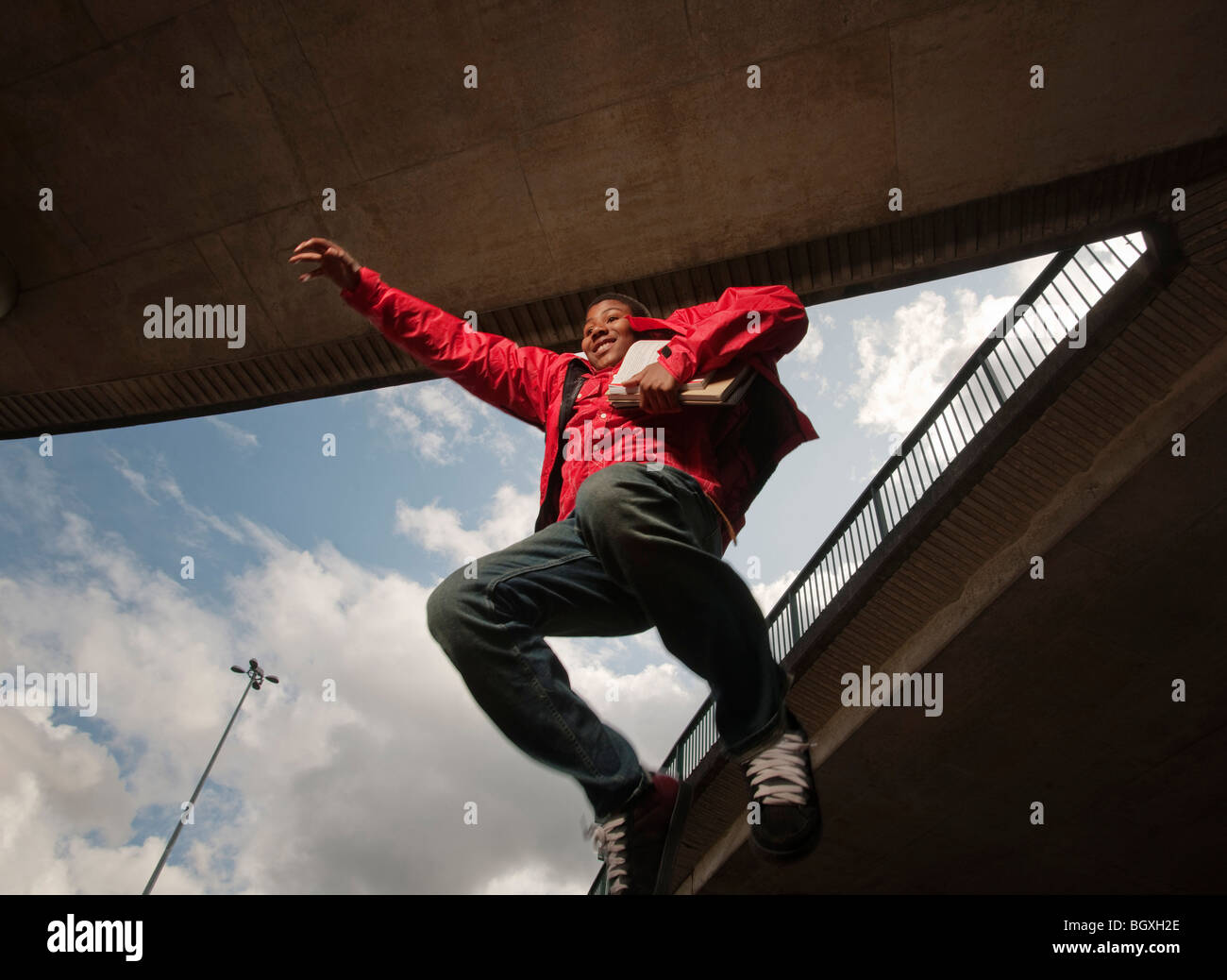 teenage boy jumping with books - Stock Image