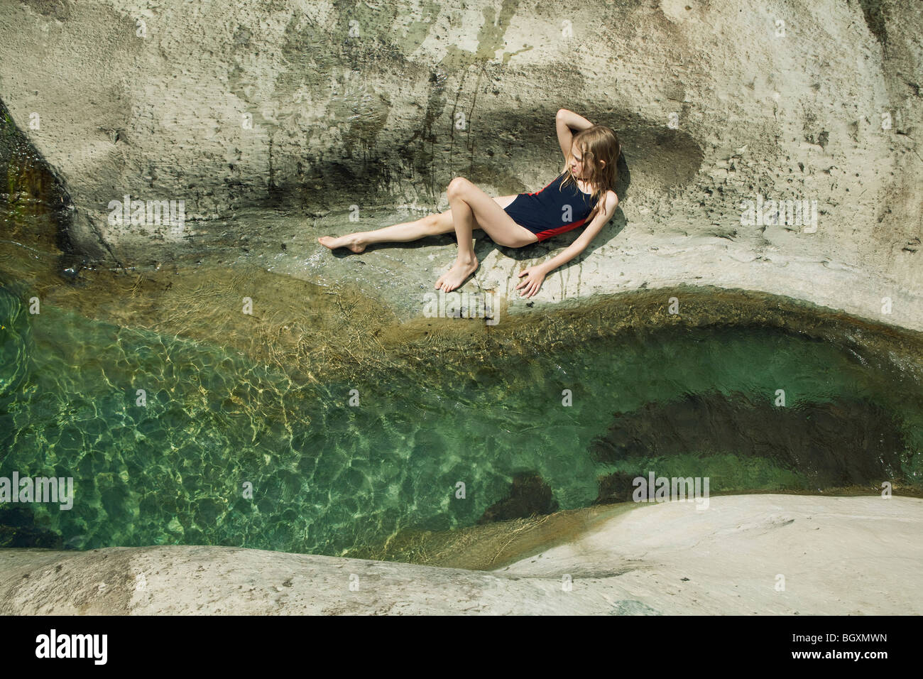 Girl lying on rock next to stream - Stock Image