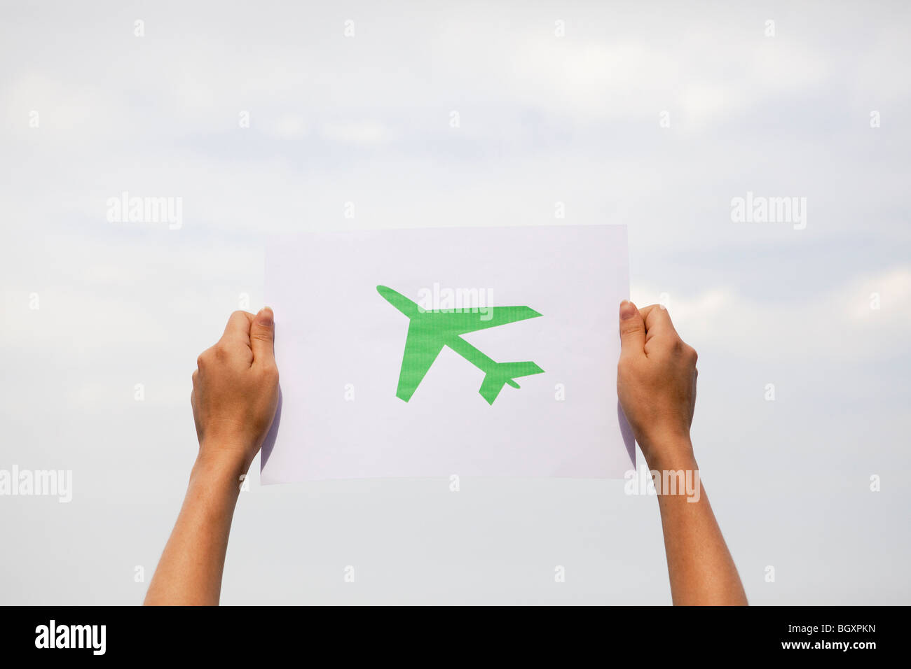 Arms holding paper green plane - Stock Image