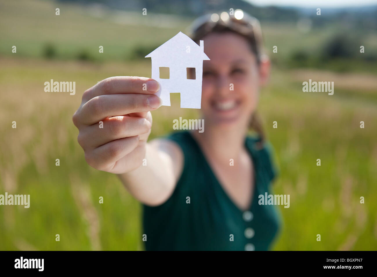 Woman raising cut-out paper house - Stock Image