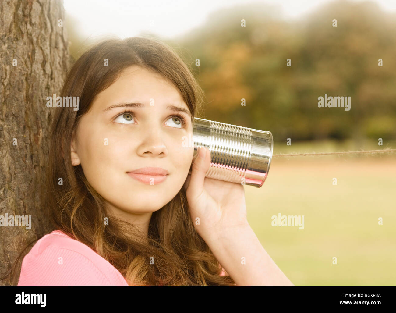 Girl Listening to Tin Can Phone - Stock Image