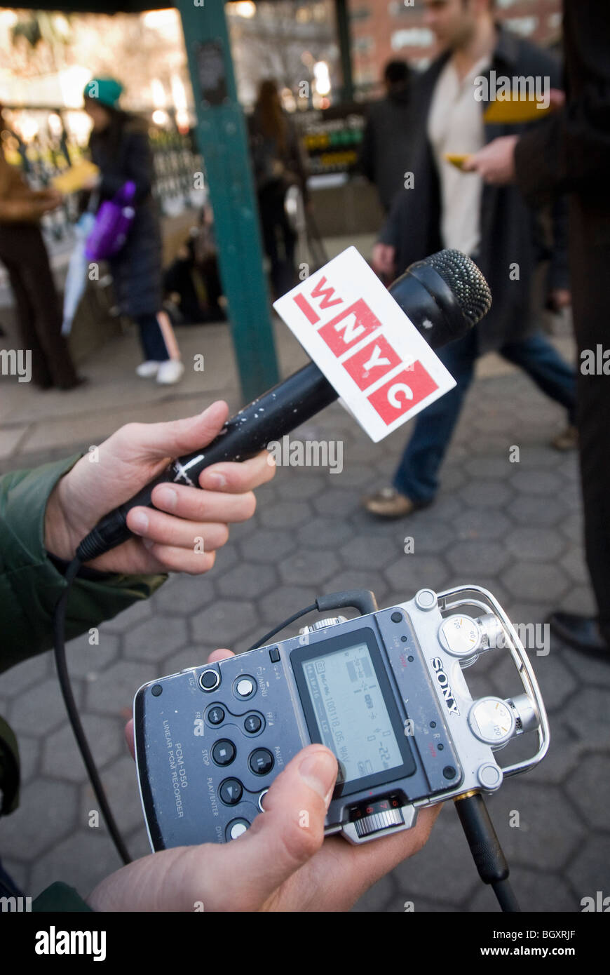 A reporter for WNYC Public Radio uses a Sony digital recorder to collect sound bites at a news event - Stock Image