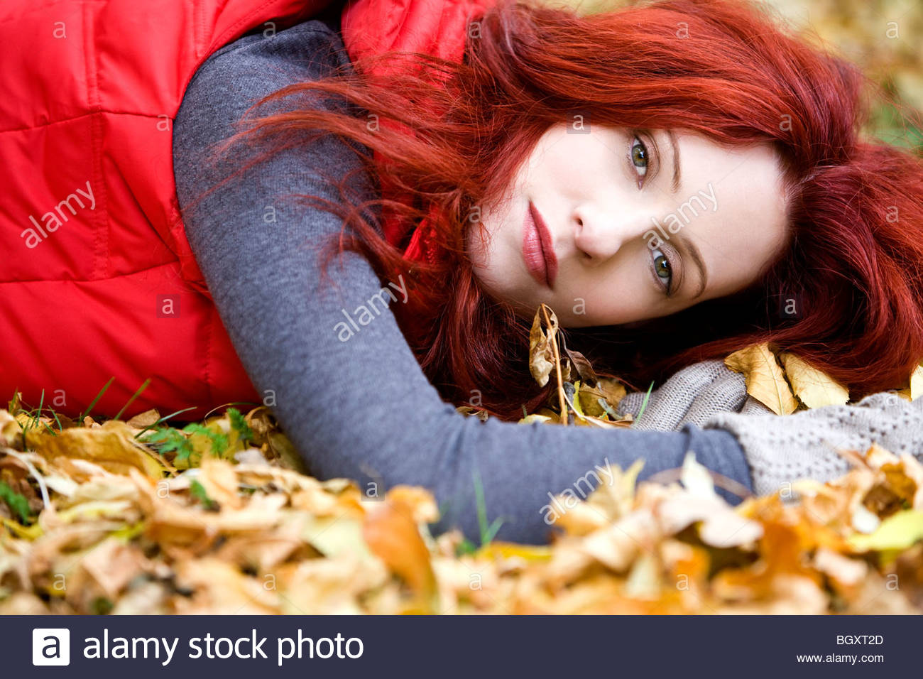 A young woman lying on autumn leaves - Stock Image