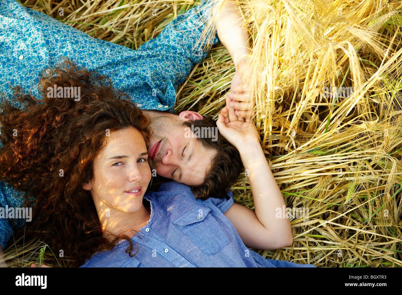 Couple laying down in a wheat field Stock Photo