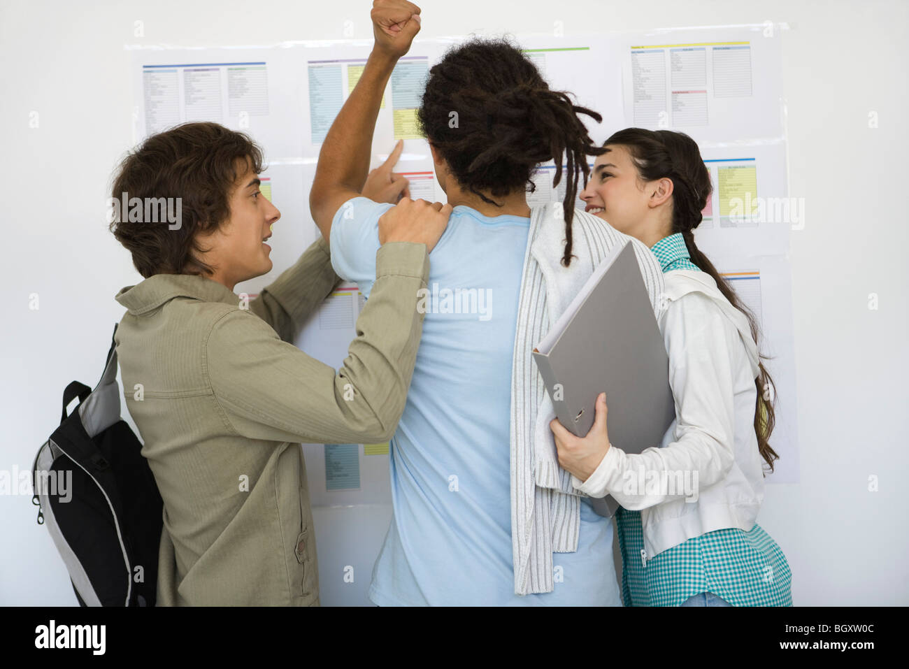 College student looking at results posted on bulletin board raising fist, classmates congratulating, rear view - Stock Image