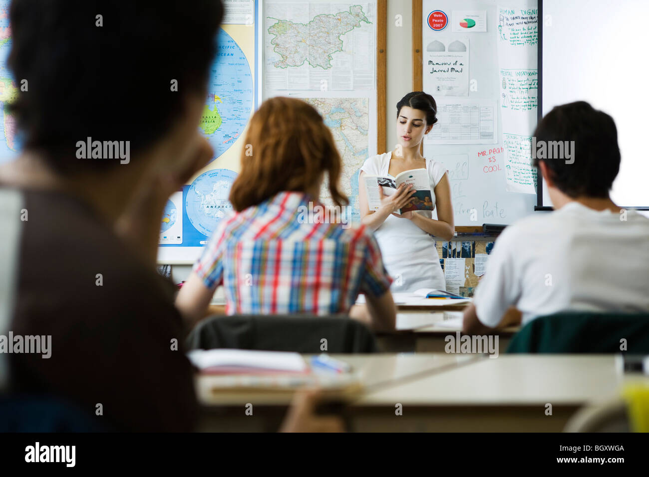 High school student reading book aloud to class - Stock Image