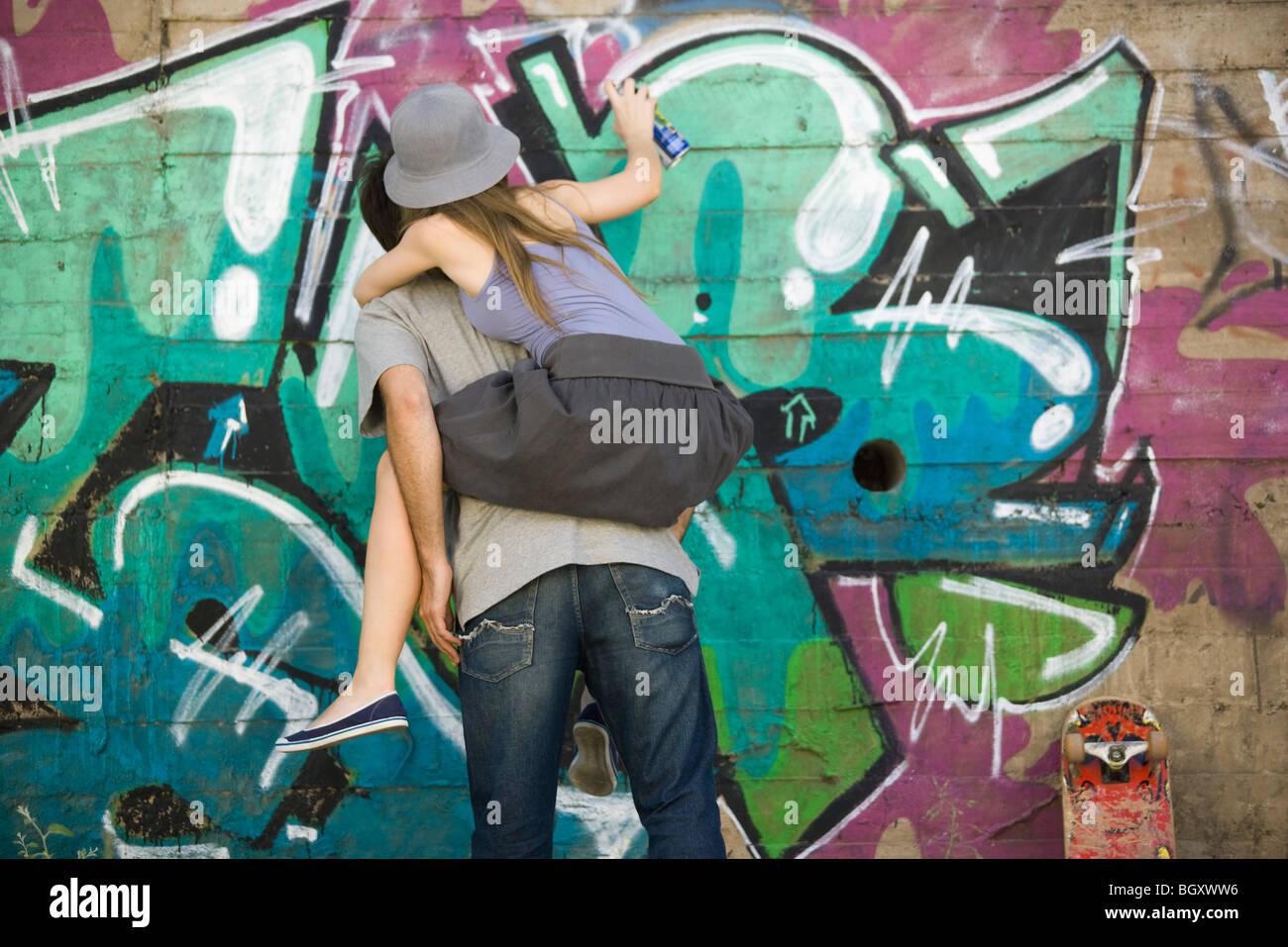 Young Woman Straddling Companions Back Spray Painting Graffiti Mural