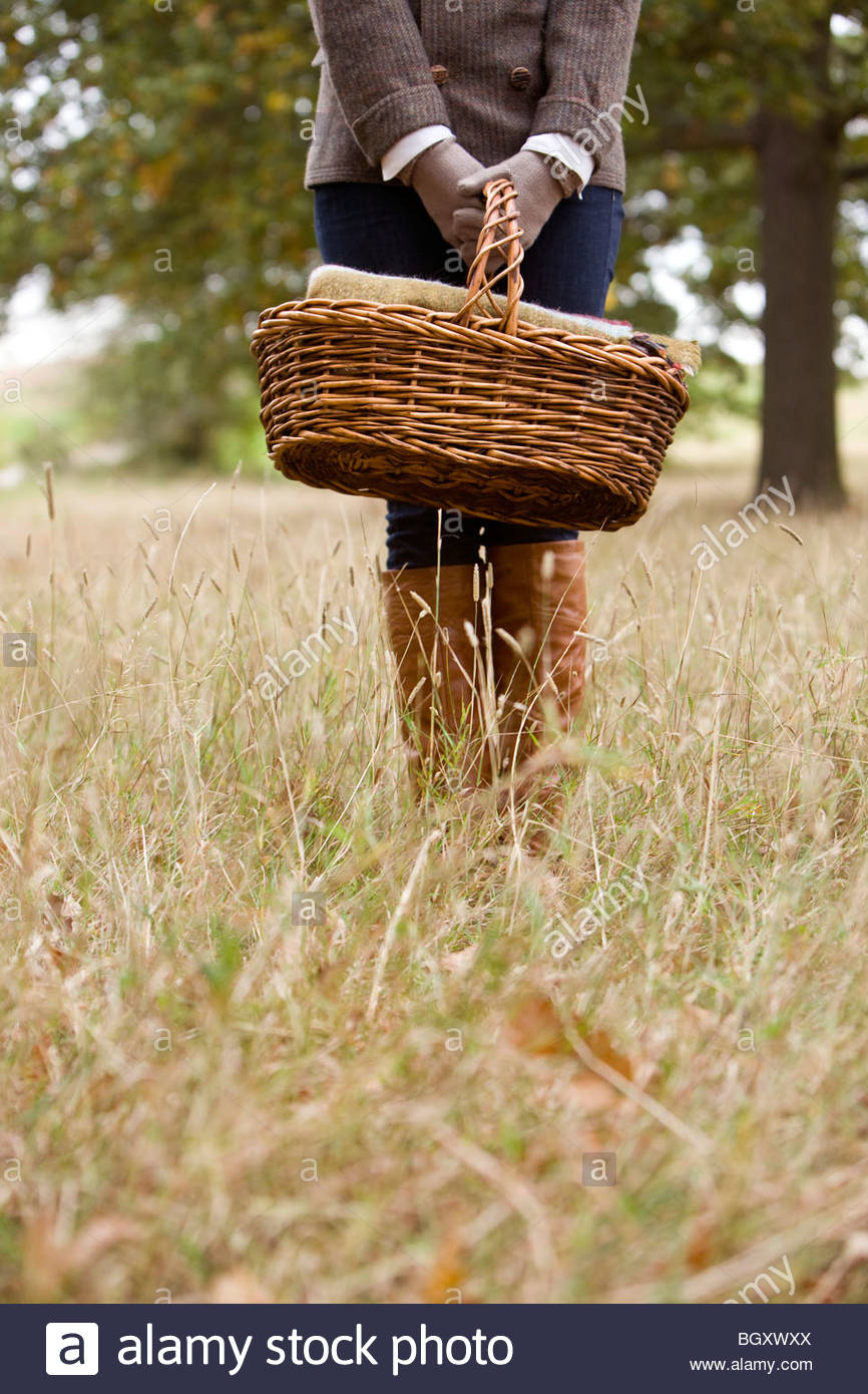 A young woman standing in a field, holding a wicker basket Stock Photo