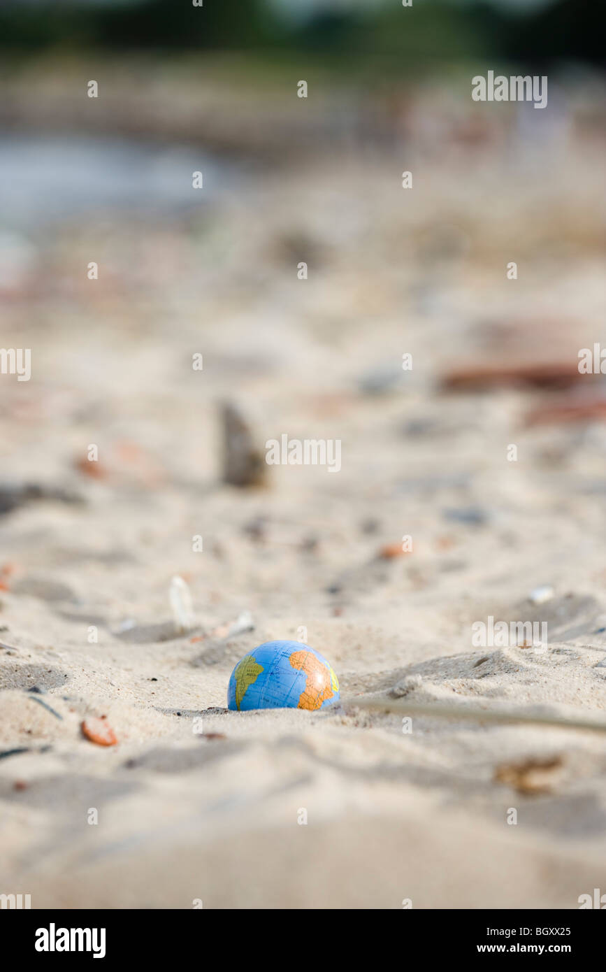 Globe partially buried in sand - Stock Image