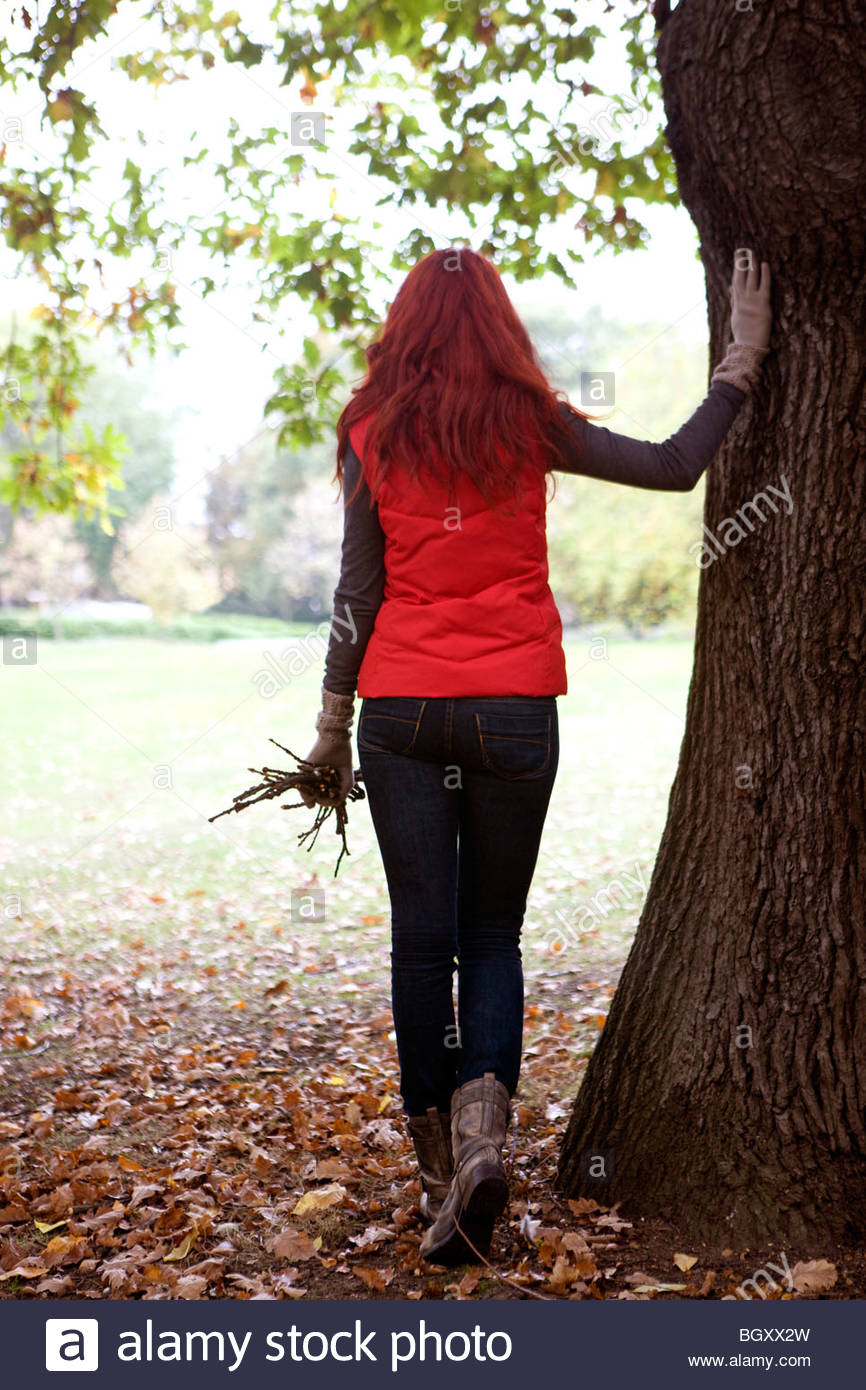 The back view of a young woman holding a handful of twigs - Stock Image