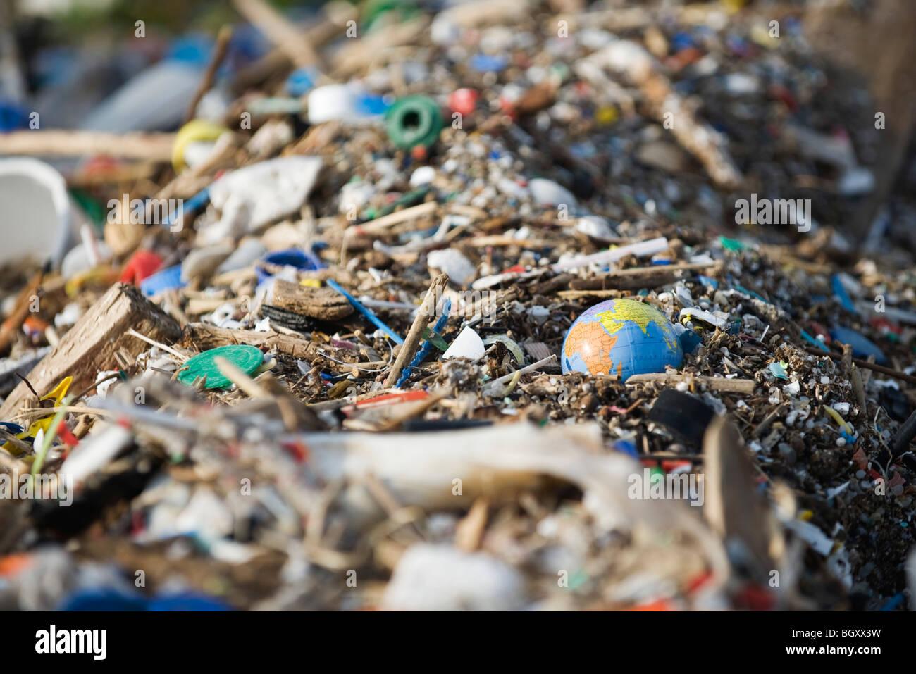 Globe in midst of landfill trash - Stock Image