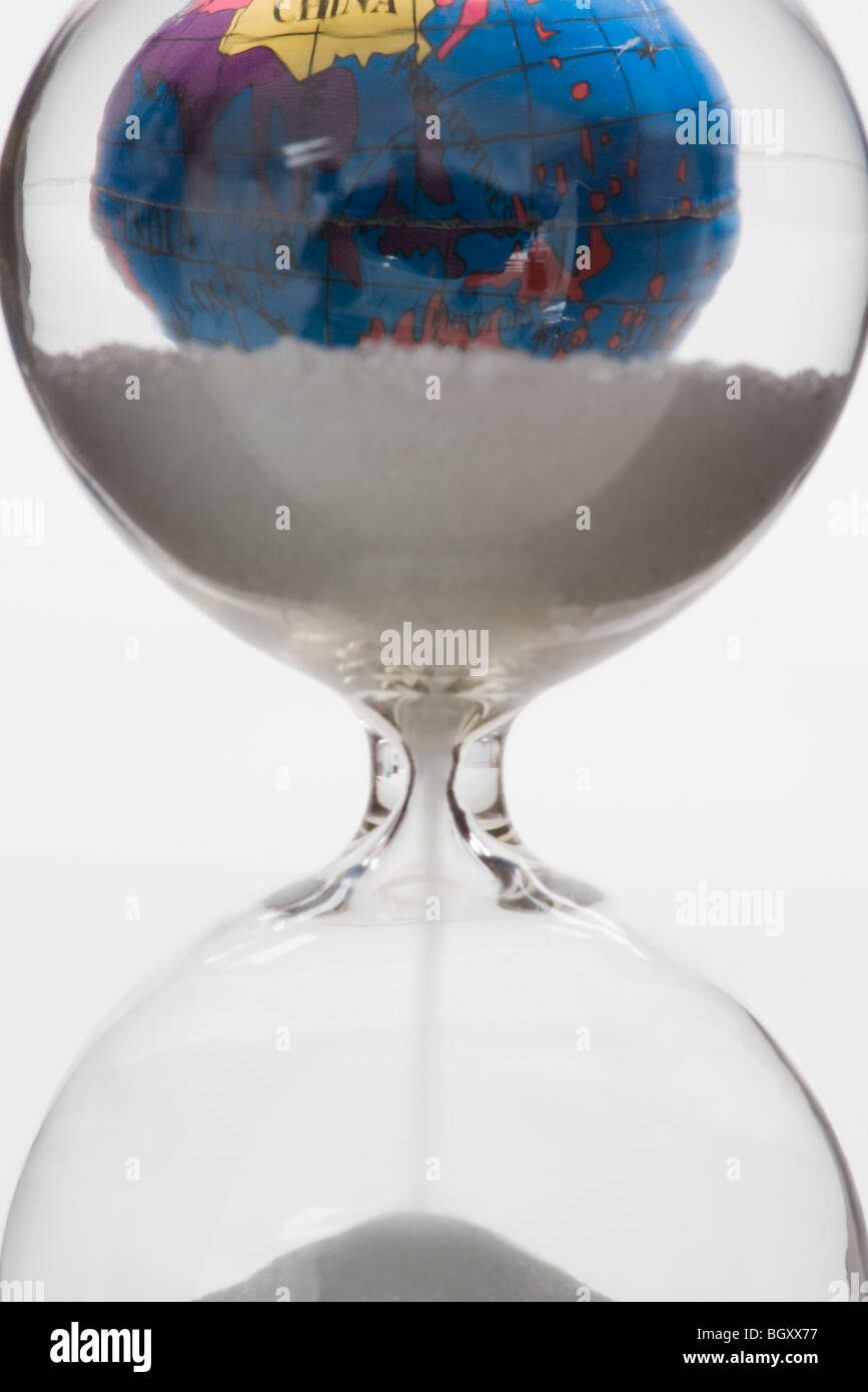 Hourglass, globe in background - Stock Image