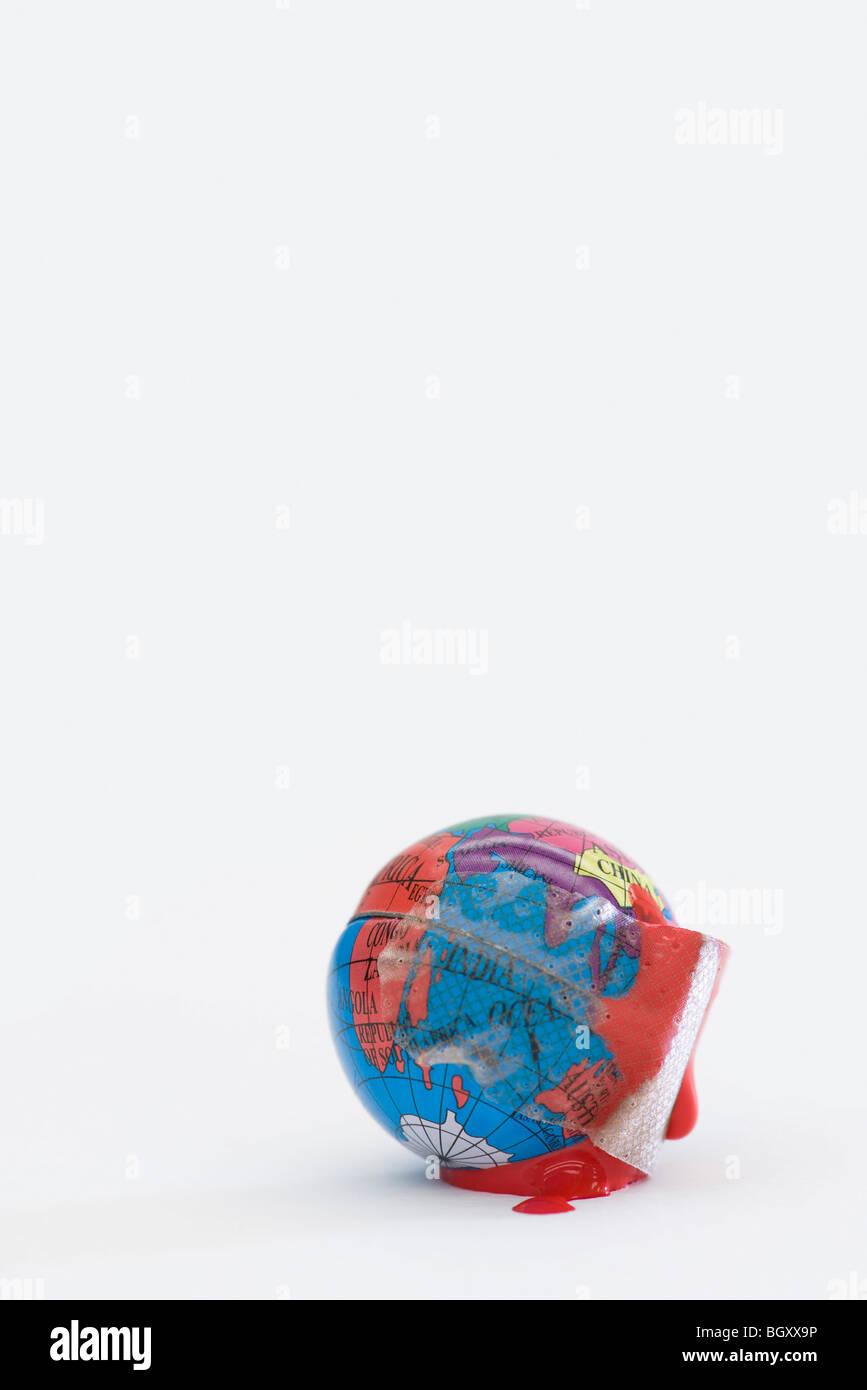 Adhesive bandage soaked in blood wrapped around globe - Stock Image