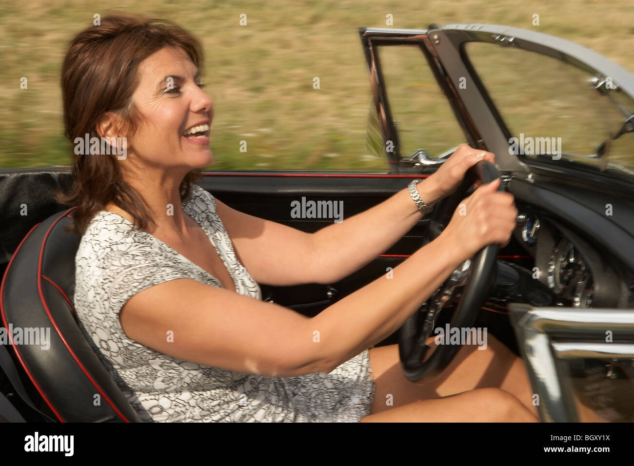 Mid aged woman in sports car - Stock Image