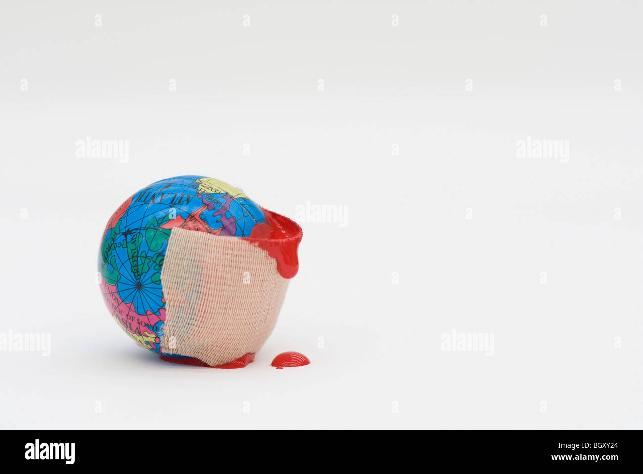 Adhesive bandage dripping blood wrapped around globe - Stock Image