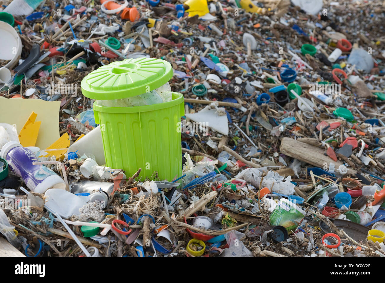 Full garbage can in midst of landfill Stock Photo