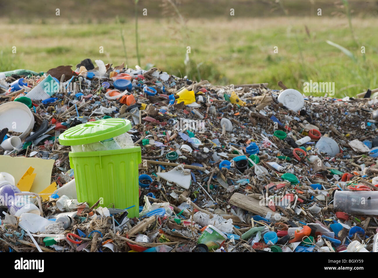 Full garbage can in midst of landfill - Stock Image
