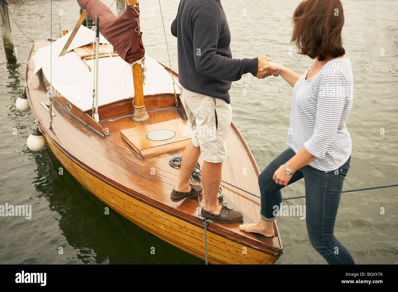 Man helping woman onto old boat - Stock Image