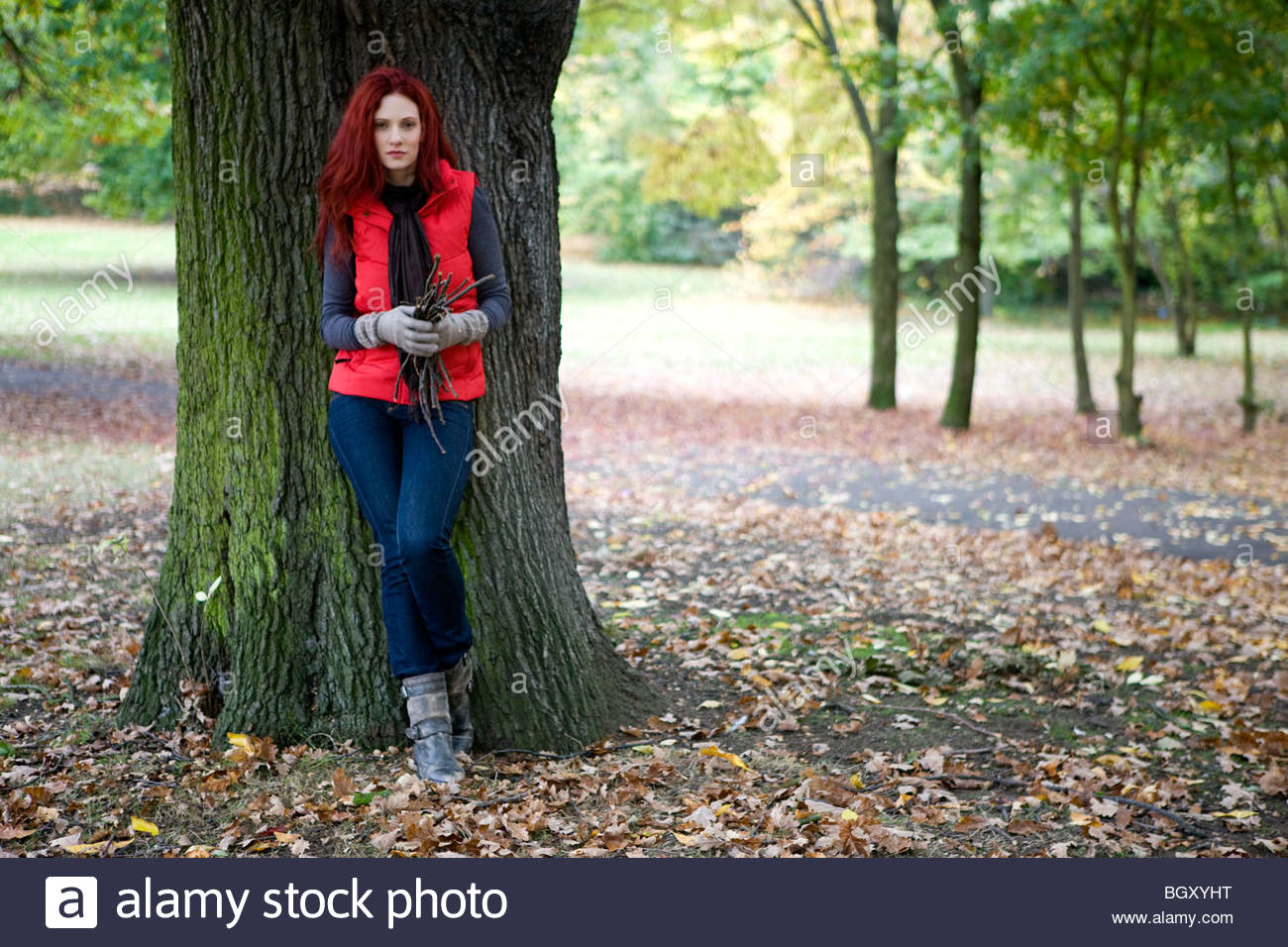 A young woman leaning against a tree, holding a handful of twigs - Stock Image