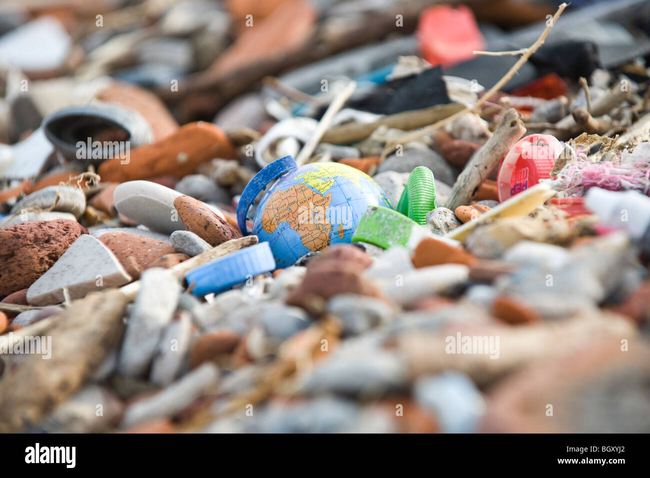 Globe surrounded and nearly covered by pile of trash - Stock Image