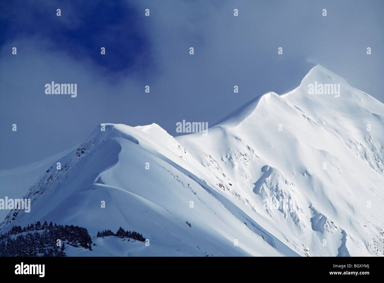 Snow cornice leading up to mountain peak - Stock Image