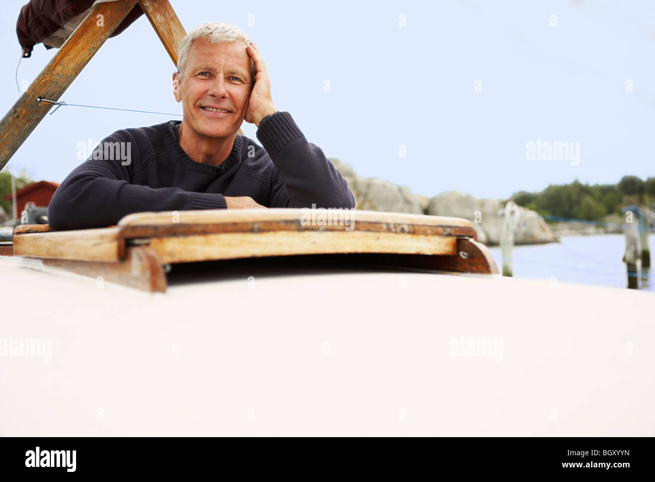 Middle aged man on old boat - Stock Image