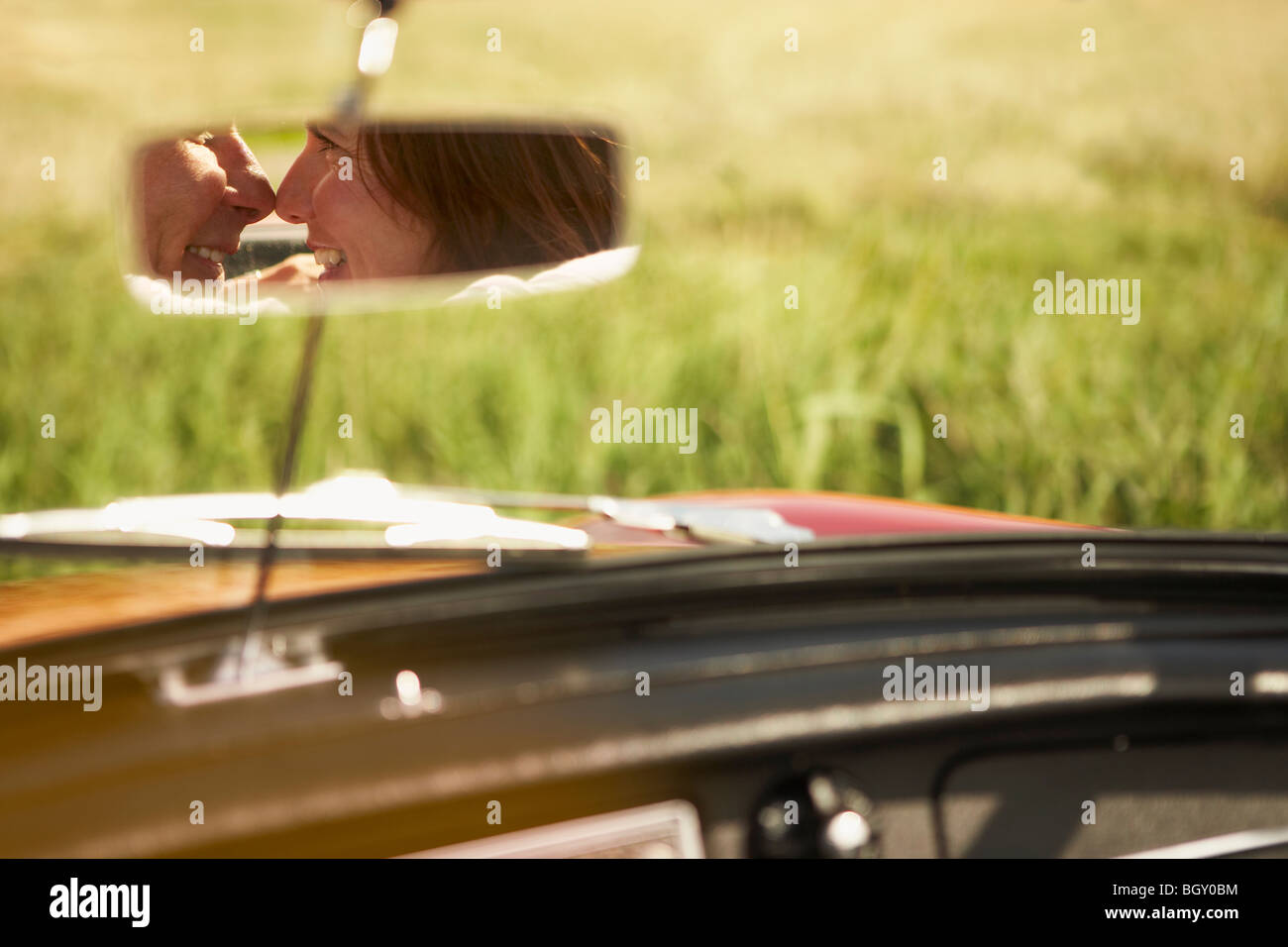 Couple in rear view mirror, will kiss - Stock Image