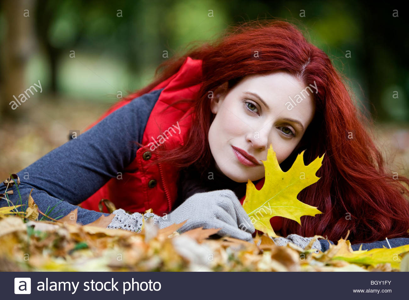 A young woman lying on the ground, holding an autumn leaf - Stock Image
