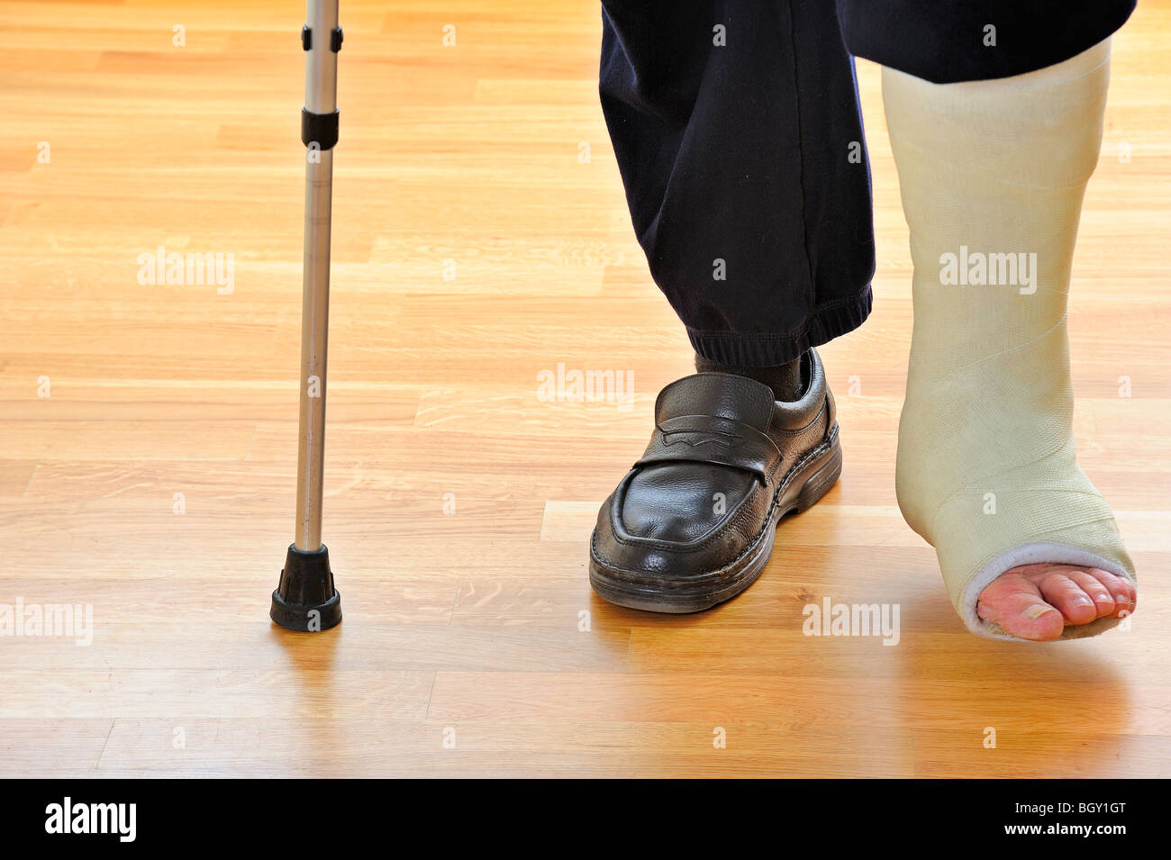 Detail of the legs and feet of a man with a broken leg, using crutches - Stock Image