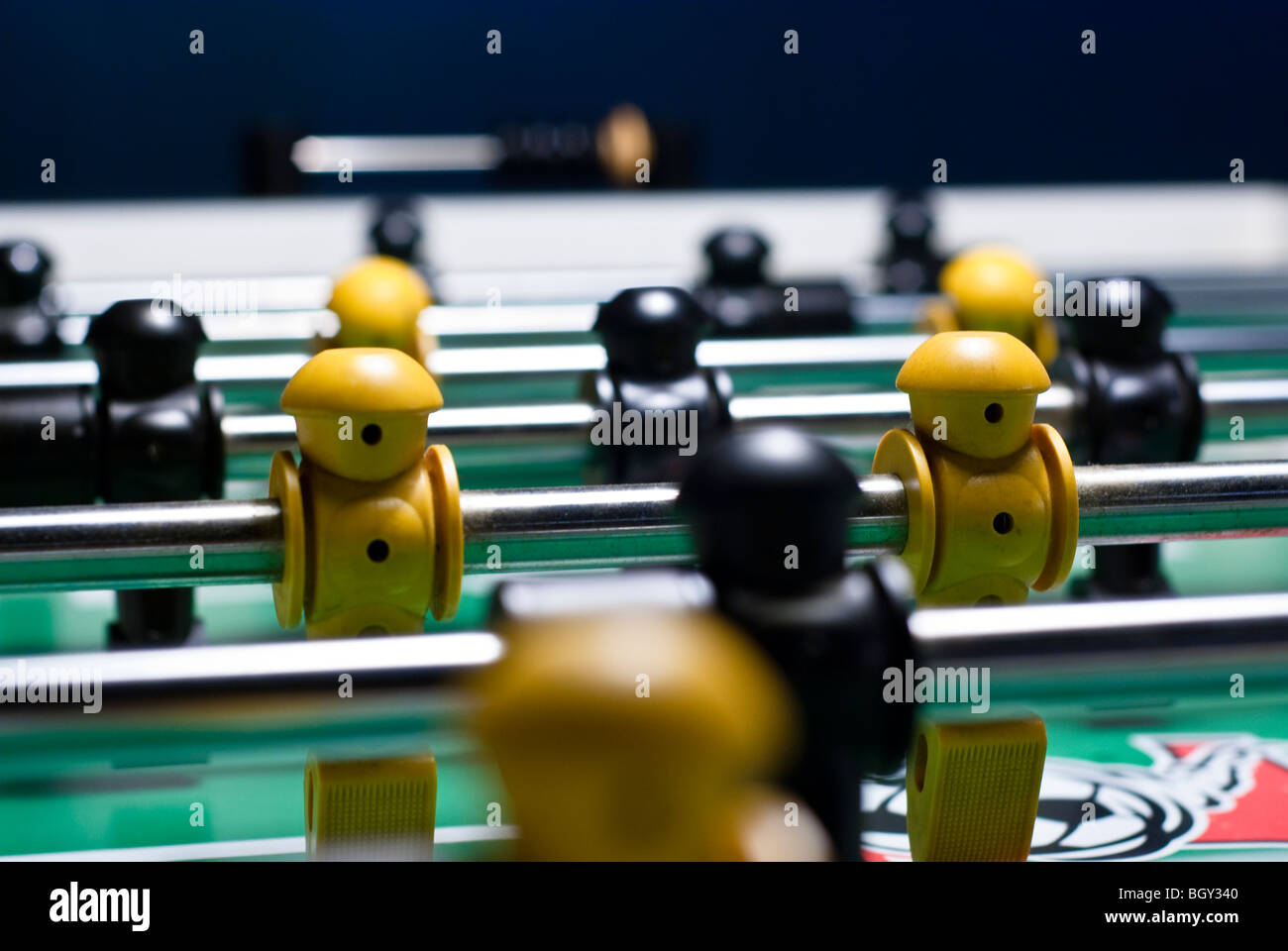 Soccer player on a soccer table, taken with shallow depth of field so only one row of yellow players is in focus - Stock Image