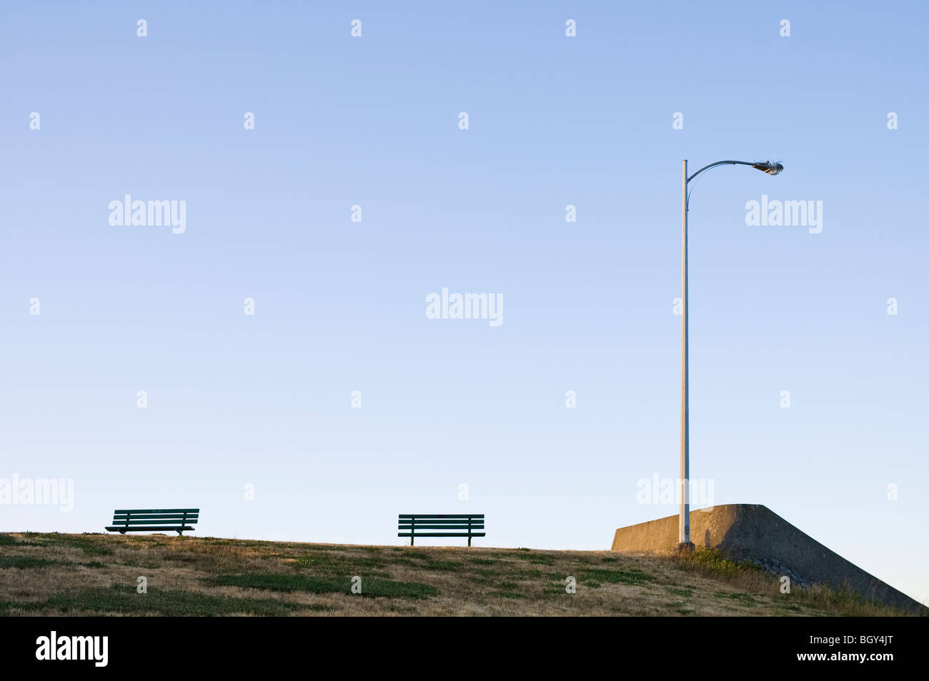 Meeting of a wall, light post and two bench at Clover point in Victoria BC Canada in the late afternoon - Stock Image