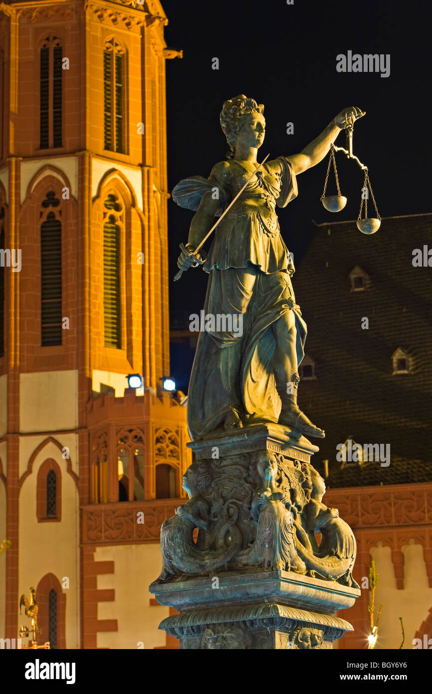 Justitia Statue (Statue of Justice) with Nikolaikirche (St Nicolas Church) in the background in the Römerberg - Stock Image