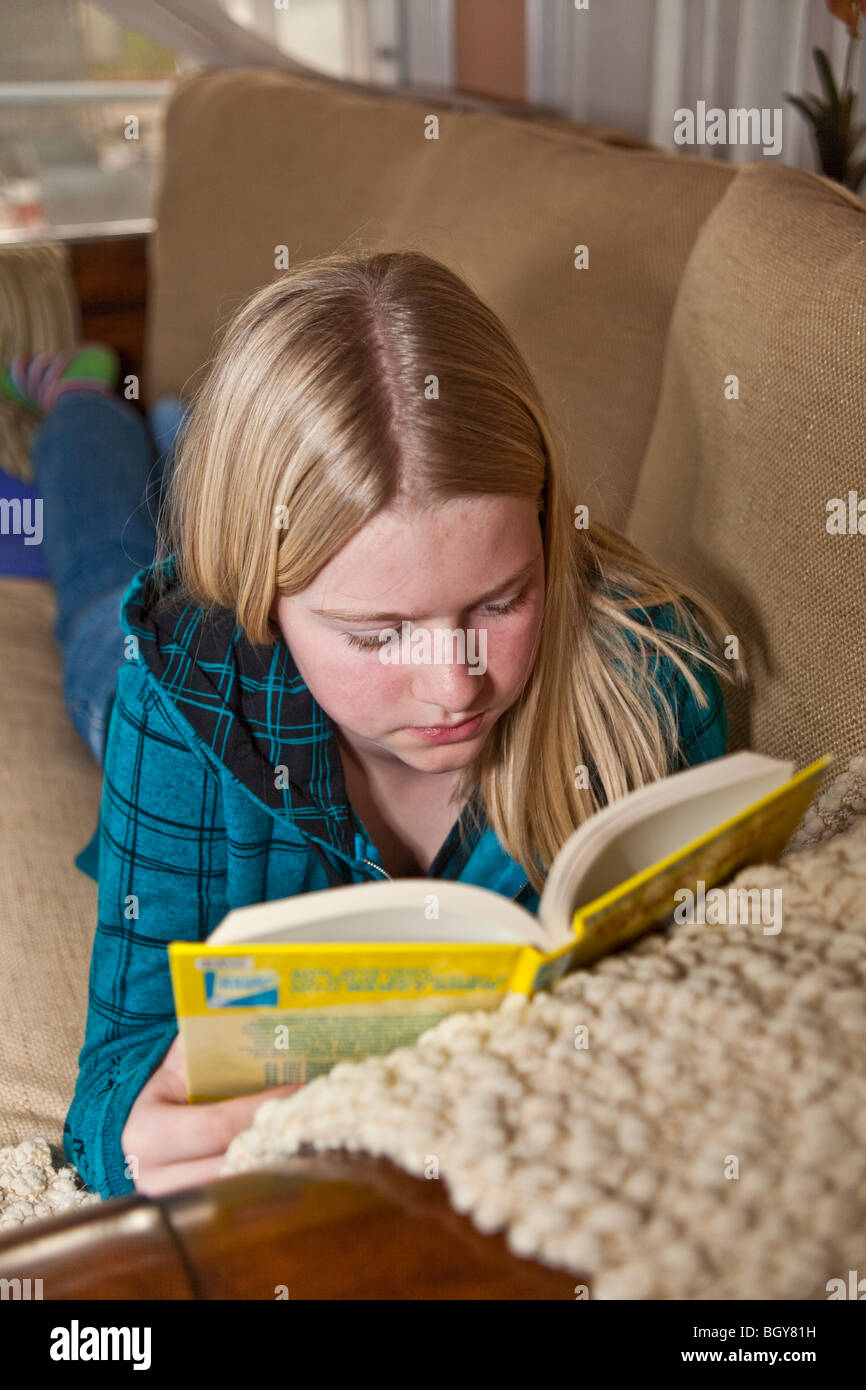 11-13 year old girl reading book on sofa at home cozy cozying rainy day activity. MR  © Myrleen Pearson - Stock Image